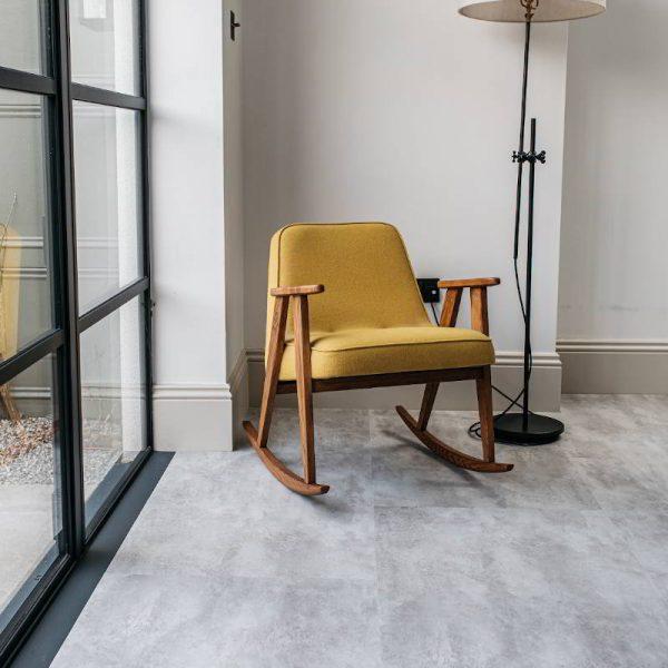 grey light stone floor alongside bifold windows and yellow chair