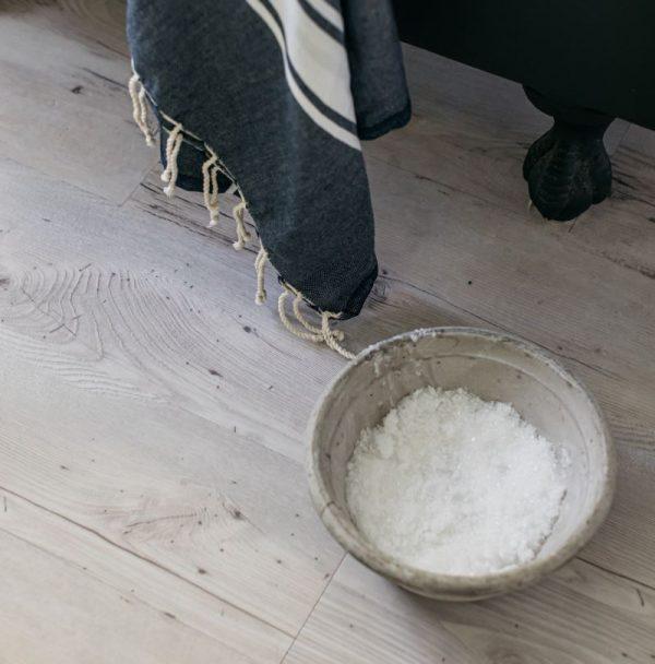 light wood bathroom floor with bath salts