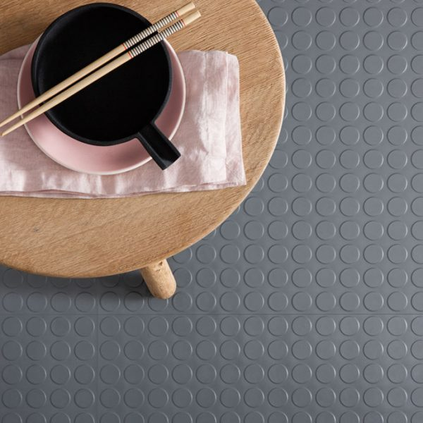 studded rubber tiles in grey with a wooden stool