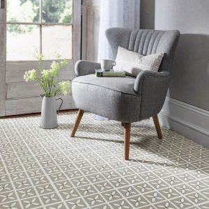 Light grey patterned floor in conservatory with grey armchair