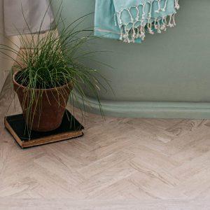 parquet white oak lvt wood effect floor with plant in neutral bathroom