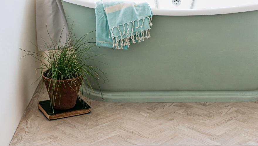 herringbone wood bathroom floor with green roll top