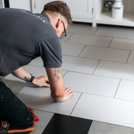 A man fitting grey vinyl tiles