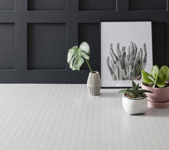 Light grey rubber flooring tiles against a panelled wall with plants