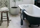 Light wood bathroom floor with a roll top bath