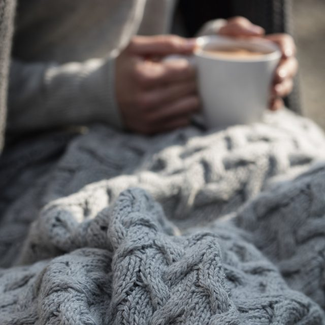 cosy autumn blanket holding coffee