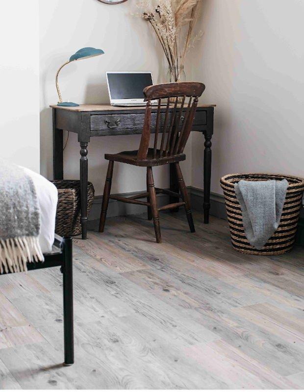 rustic desk set up in bedroom with wooden floor