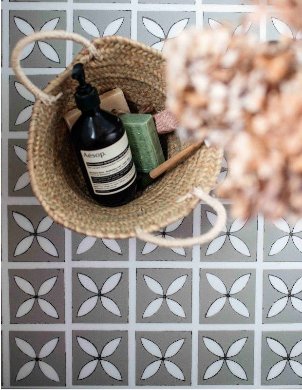 lattice patterned bathroom flooring with luxury handwash and blossom