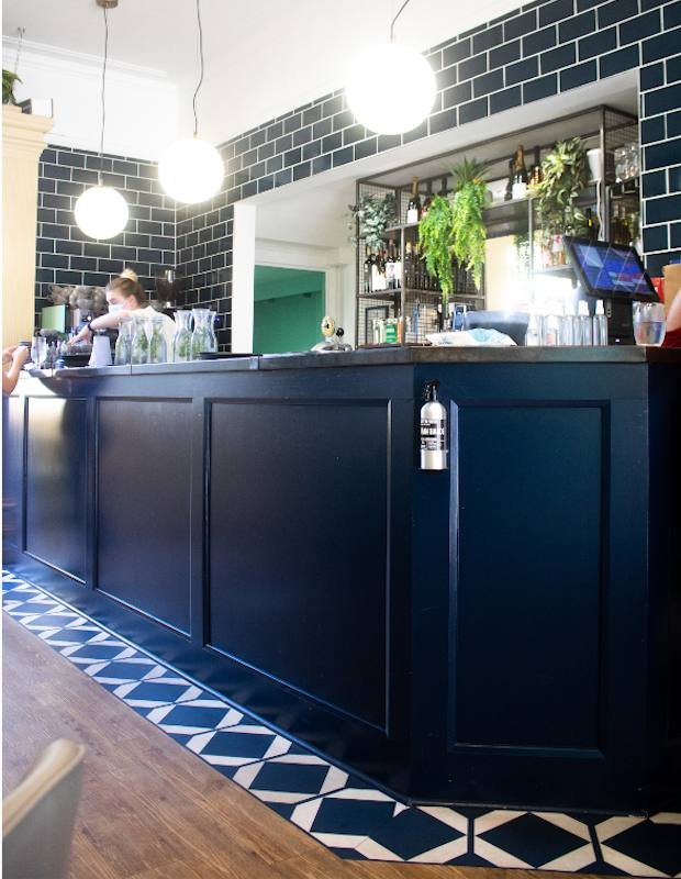 decorative blue floor tiles bordering the bar at jo and co