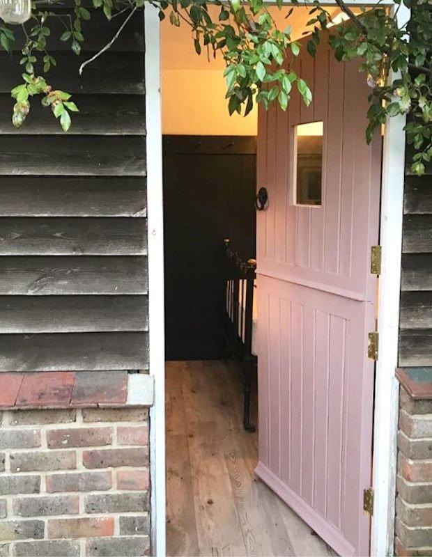 garden room with vinyl floor and pink door