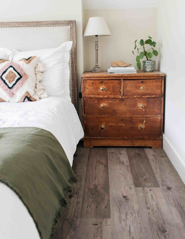 bedroom with wood plank floor and green throw