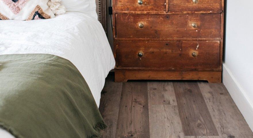 ashy vinyl plank bedroom floor with antique dresser