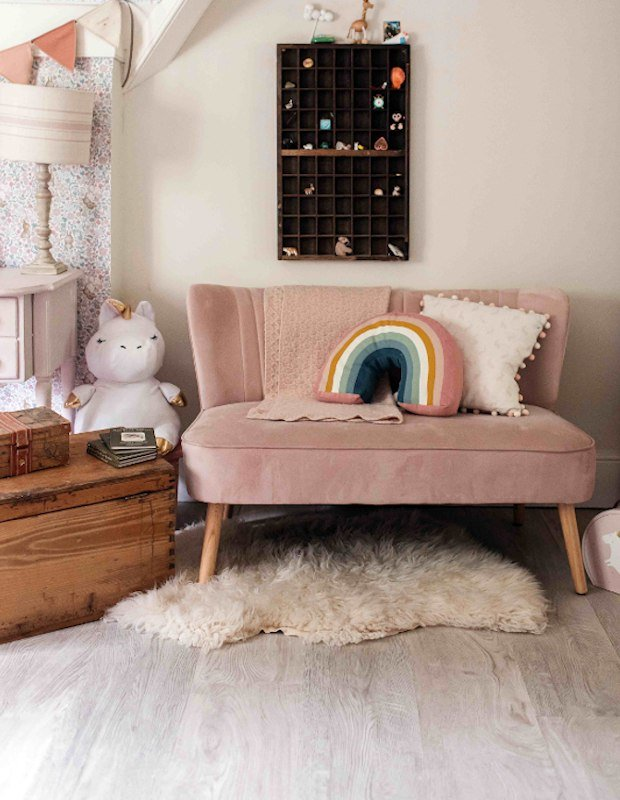 childrens room with a pink velvet sofa and toys