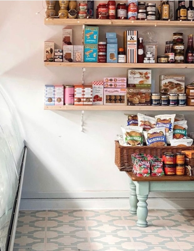 deli with decorative light blue floor tiles and stocked shelves