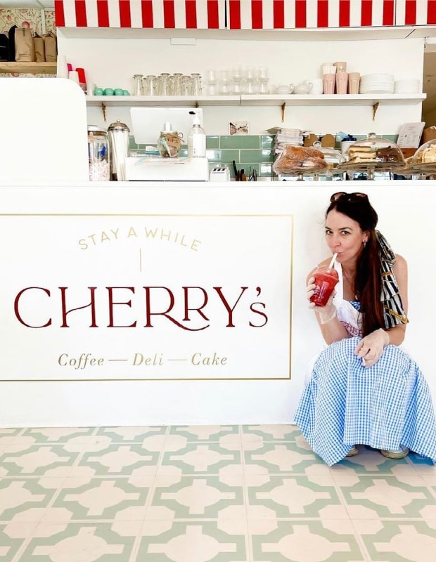 deli owner sitting next to the cherry's logo with a smoothie and decorative flooring
